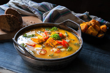 Pumpkin soup with tomatoes and herbs in a rustic style.