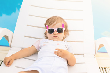 Endless summer! Cute baby relaxing at sunbed near pool, resort.