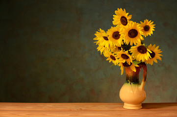 Sunflower in the ceramic vase on a wooden table
