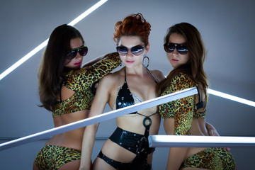 Three sexy girls in glasses and neon lamps