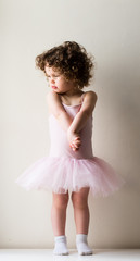 Toddler girl with curly hair in pink tutu and white socks with hands clasped in front against neutral background