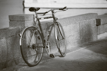 close up vintage bicycle laying near a wall,sepia process,black and white picture style,dark edges,selective focus