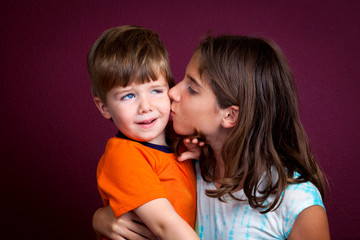 Boy Recoils From His Older Sister Who Is Kissing Him