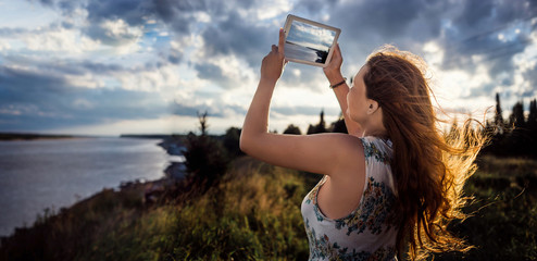 Young girl with the hair fluttering on wind photographing  digital tablet beautiful river landscape in summer evening, woman taking photo  touch pad camera during recreation time. Panoramic view.