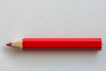 Red pencil on paper background