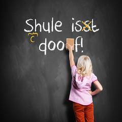 kleines Mädchen korrigiert Satz auf Tafel