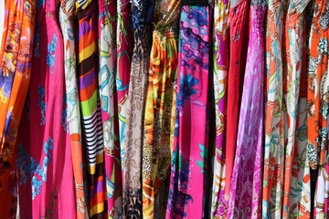 Rack of colorful dresses at an outdoor flea market