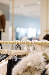 Interior of fashion clothing shop with clothes, bags and shoes