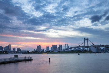 cityscape and skyline of tokyo from water at sunset