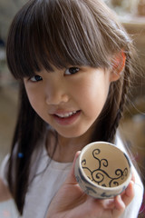 Little Asian girl showing her hand craft bowl made by clay
