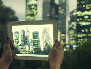 In the bottom left of the photo are hands holding tablet, whose screen contains color photo of Moscow-city business center, urban people concept close up
