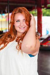 Portrait of a young, smiling plus size woman with long red hair.