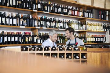 Salesman Assisting Customer In Buying Wine In Supermarket