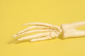 skeleton human hand on yellow background