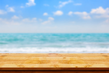 Empty top of wooden table on blurred beach background.