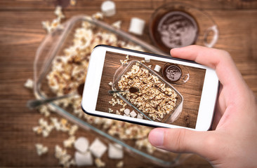 Hands taking photo dark chocolate caramel popcorn with smartphone.
