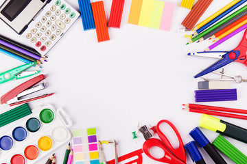 Various office supplies arranged as frame on a white background. Back to school. Top view with copyspace
