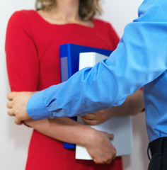 Sexual harassment at work. Boss touching his secretary in office.