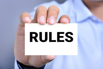 RULES word on the card shown by a man