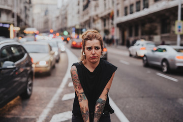 Tattooed blonde girl making faces while standing in the middle of road