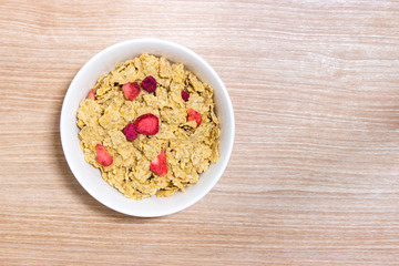 Cereal with strawberry in white bowl on wooden table