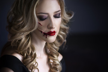 Beautiful young blonde woman in black dress with halloween make up and bloody face art, victim of domestic violence