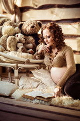 Attractive pregnant woman lying on fur and reading book in a wooden house.