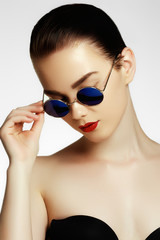 Beauty portrait of beautiful brunette model woman with stylish hairstyle in sunglasses. Professional makeup. Fashion model in sunglasses. Fashion and accessories concept