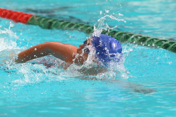 Young Asian man wearing blue cap practice freestyle stroke in a swimming pool