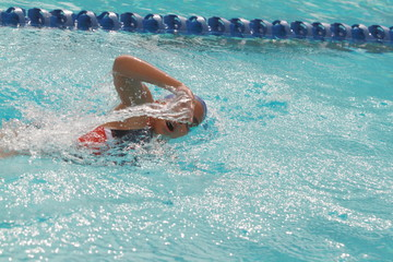 Young Asian woman wearing blue cap swimmer practice freestyle stroke in a swimming pool for competition
