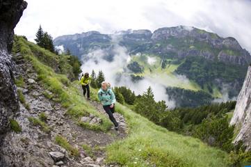 Man and woman hiking, Appenzellerland, Switzerland.