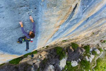 A climber tries hard high up on a cliff.