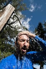 Man rinsing off under an outdoor shower, Cook Islands.