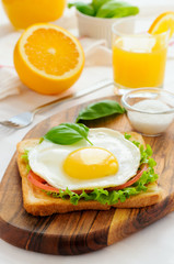 Sandwich with fried egg, tomato, green salad