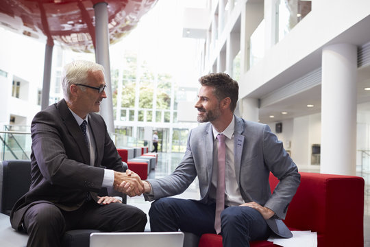 Two Businessmen Shaking Hands In Lobby Of Modern Office