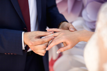 Bride and groom exchanging of wedding rings at wedding ceremony