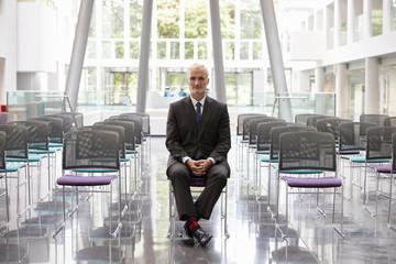 Businessman In Empty Auditorium Preparing To Make Speech