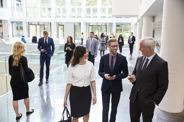 Businesspeople In Busy Lobby Area Of Modern Office