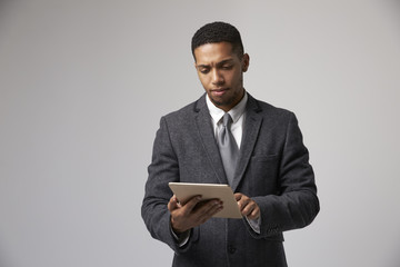 Studio Portrait Of Businessman Using Digital Tablet