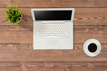 Overhead shot of office table with white laptop, coffee cup and green plant