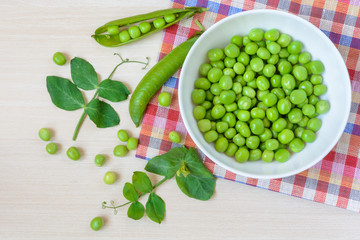 Fresh green peas in white ceramic bowl on wooden background. Top view.
