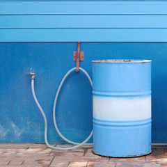 Blue water tank parti-color and rubber tube with wooden wall