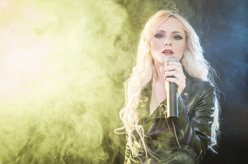 Young beautiful woman singing in colourful smoke