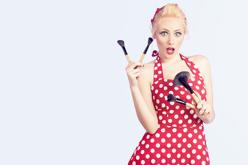 Girl makeup holding brushes with a pin up red dress