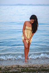 Girl standing in the water lifting her dress up