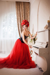 Pretty woman dressed in red evening gone, leather corset and flowers crown near the piano.