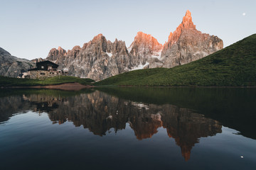Mountains reflected in water with cabin