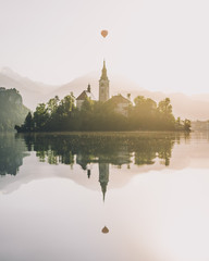 Island reflected in water with hot air balloon