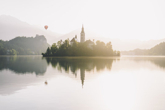 Island reflected in water with hot air balloon, distant
