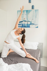 Woman doing yoga exercises in bed